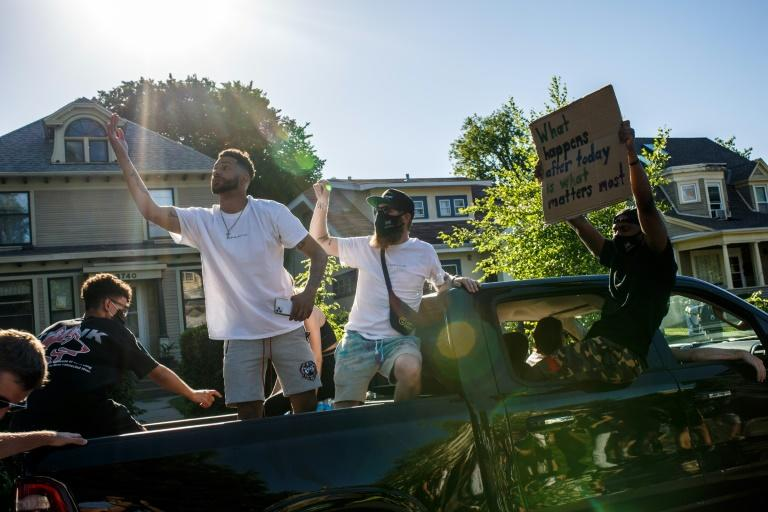 Protesters drive by in a car during a demonstration over the death of George Floyd in Minneapolis, Minnesota