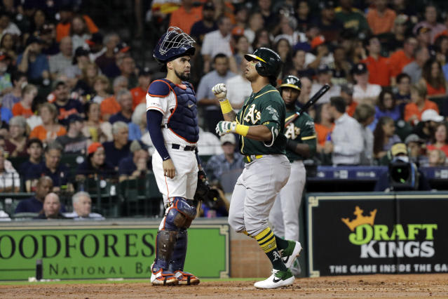 Oakland Athletics' Khris Davis, right, celebrates after hitting a two-run home run as Houston Astros catcher Robinson Chirinos stands behind home plate during the second inning of a baseball game Tuesday, Sept. 10, 2019, in Houston. (AP Photo/David J. Phillip)