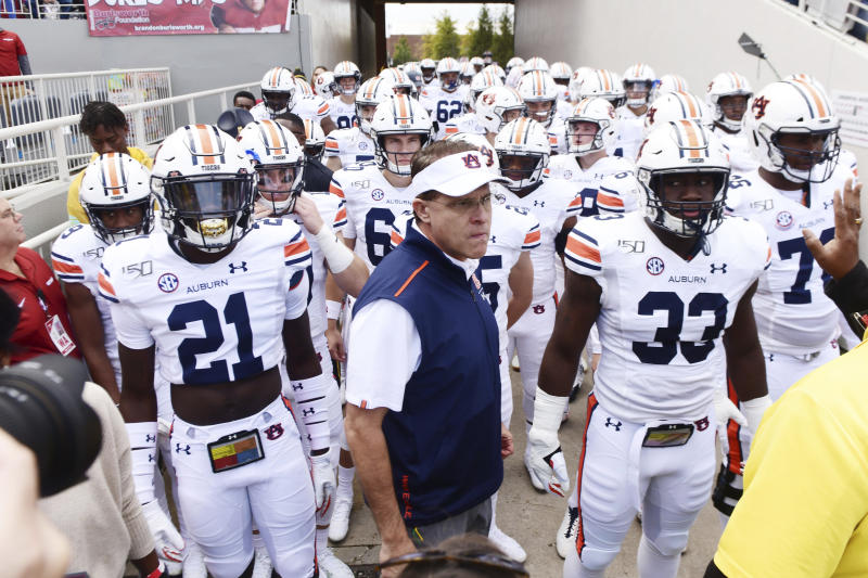 Auburn coach Gus Malzahn leads his team onto the field against Arkansas during an NCAA college football game, Saturday, Oct. 19, 2019 in Fayetteville, Ark. (AP Photo/Michael Woods)