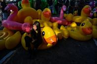A Thai pro-democracy protester poses with inflatable yellow ducks that have become a symbol of the movement
