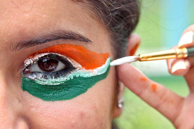 A college girl gets her eye painted in tri-colours of India's national flag on the eve of the country's Independence Day celebrations in the northern Indian city of Chandigarh August 14, 2012. REUTERS/Ajay Verma