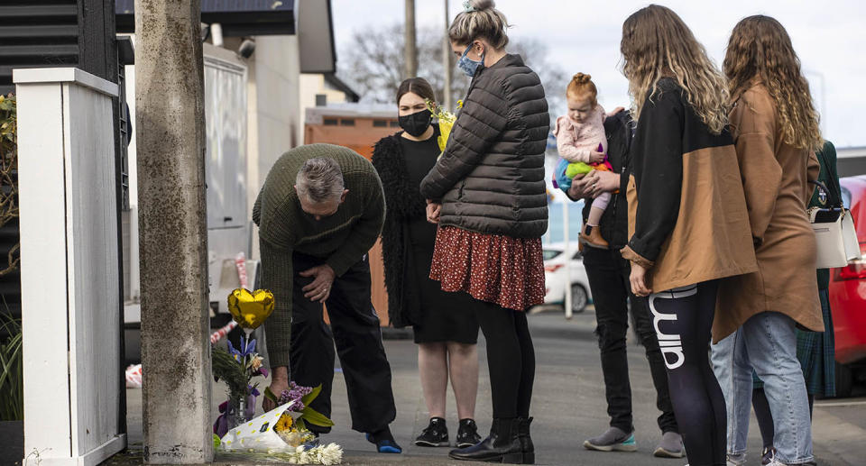 People lay flowers outside of a house where three children were found dead in the South Island town of Timaru. Source: George Heard/New Zealand Herald via AP