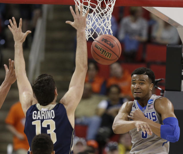 Memphis guard Chris Crawford (3) passes the ball against George Washington guard/forward Patricio Garino (13) during the second half of an NCAA college basketball second-round tournament game, Friday, March 21, 2014, in Raleigh. (AP Photo/Chuck Burton)