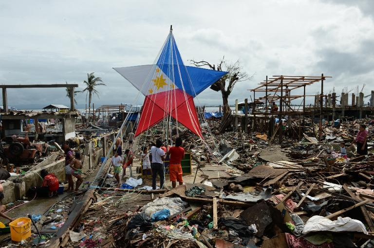 Residents and survivors of Super Typhoon Haiyan decorate a giant lantern in Tacloban, Philippines on December 24, 2013