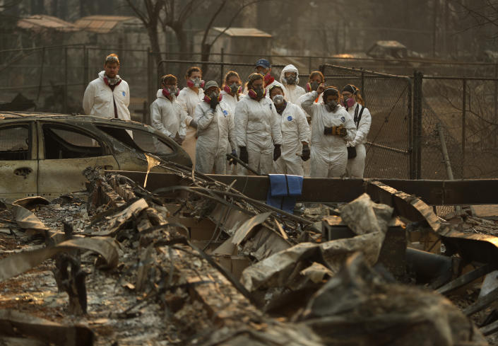 <p>Anthropology students observe as human remains are recovered from a burned out home at the Camp Fire on Nov. 11, 2018, in Paradise, Calif. (Photo: John Locher/AP) </p>