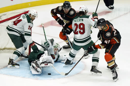 Minnesota Wild goaltender Cam Talbot, bottom left, stops a shot by the Anaheim Ducks during the second period of an NHL hockey game Monday, Jan. 18, 2021, in Anaheim, Calif. (AP Photo/Marcio Jose Sanchez)