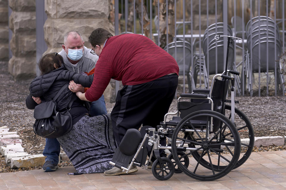 Lucas Christensen, right, helps Rodney Wegg pick up his wife, Kari, after she collapsed after visiting IU Health North Hospital for her second COVID shot in Carmel, Ind., on Monday, March 22, 2021. (AP Photo/Charles Rex Arbogast)