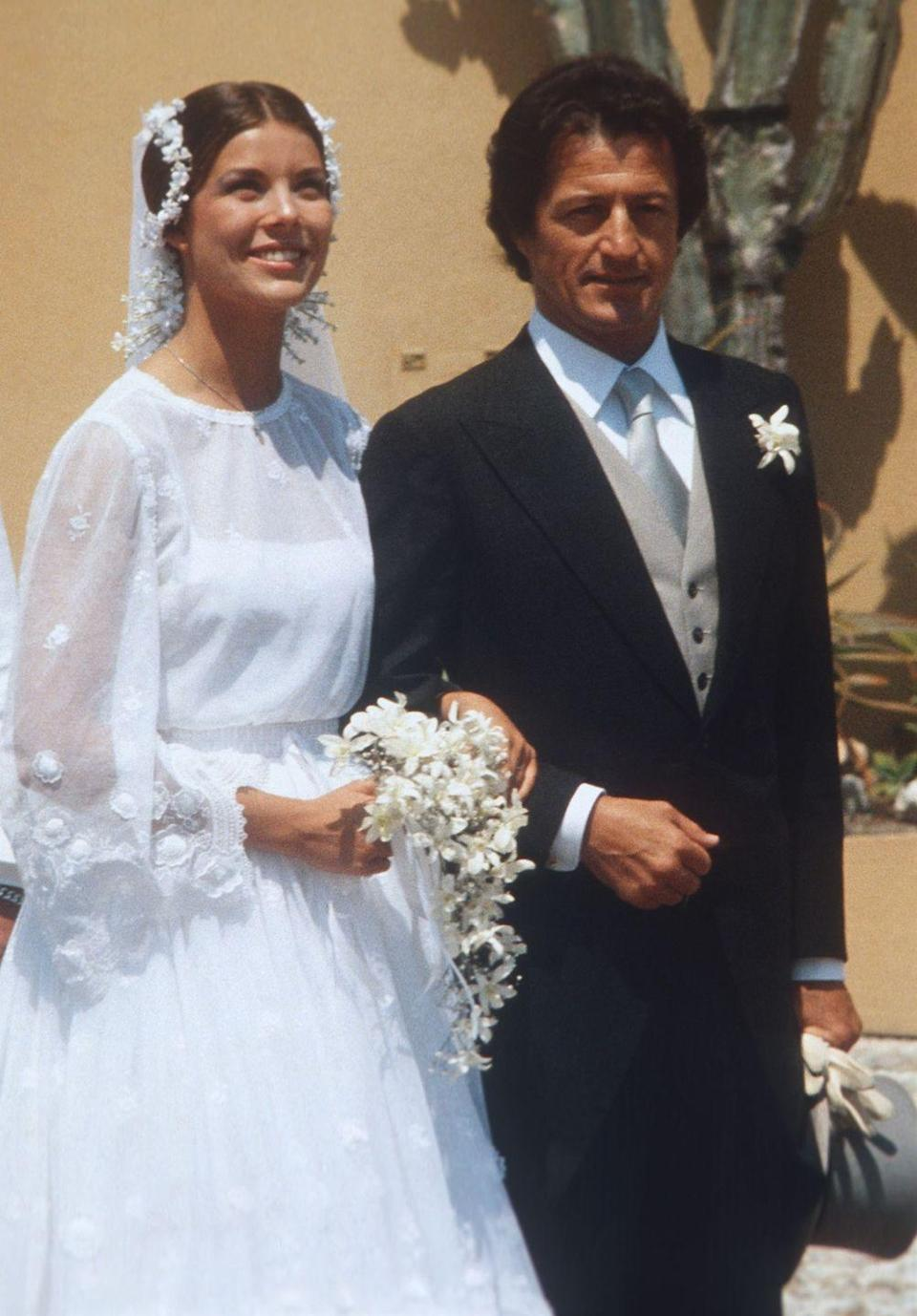 <p>Princess Caroline, Grace Kelly's daughter, wore a 70's-era dress with a floral crown for her first wedding (she would have two more).</p>
