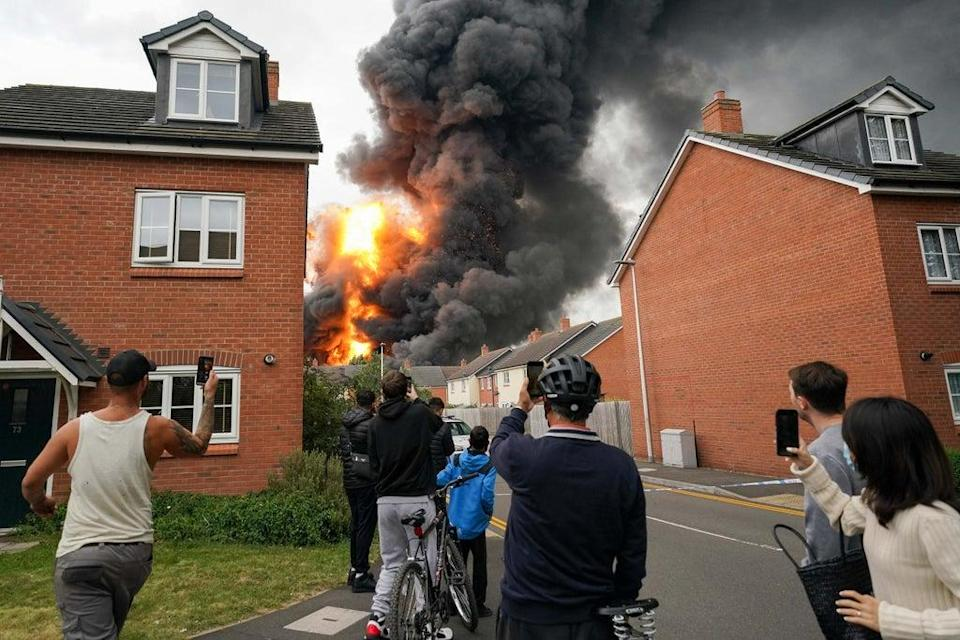 Residents watch an explosion during the fire (Jacob King/PA) (PA Wire)