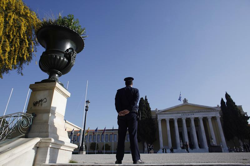 A police officer stands in front of Zappeion hall during a Eurogroup meeting, in Athens on Tuesday, April 1, 2014. Finance ministers from the eurozone and the wider European Union are gathering in Athens amid tight security, with Greece hoping for a gesture of support for the release of long-delayed funds from the country's multi-billion-euro bailout. (AP Photo/Kostas Tsironis)
