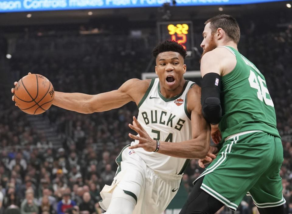 """File-This May 8, 2019, file photo shows Milwaukee Bucks' Giannis Antetokounmpo driving past Boston Celtics' Aron Baynes during the first half of Game 5 of a second round NBA basketball playoff series in Milwaukee. Leading the Bucks' resurgence is MVP candidate Antetokounmpo, a fan favorite and a source of pride for Milwaukee's Greek community. Antetokounmpo was born in Athens, Greece.""""It's important for the Greek community to be able to gather together as a unit and celebrate him. And he in turn celebrates us,"""" said Tim Stasinoulias, 61, a Bucks fan since the team came to Milwaukee in 1968.(AP Photo/Morry Gash, File)"""