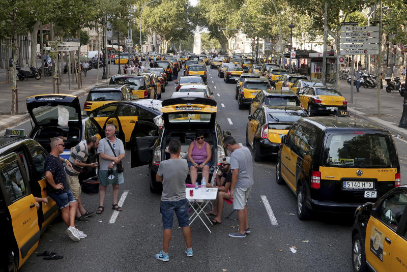 Taxi drivers block the Gran Via avenue in Barcelona, Spain, Monday, July 30, 2018. Taxi drivers in Barcelona are blocking traffic on a major thoroughfare as part of an indefinite strike to protest the use of ride-hailing apps like Uber and Cabify. (AP Photo/Manu Fernandez)