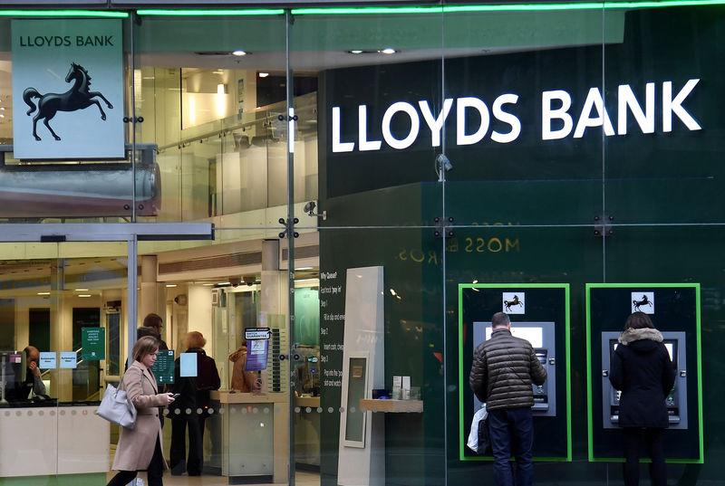 FILE PHOTO: Customers use ATMs at a branch of Lloyds Bank in London, Britain, February 21, 2017. REUTERS/Toby Melville/File Photo