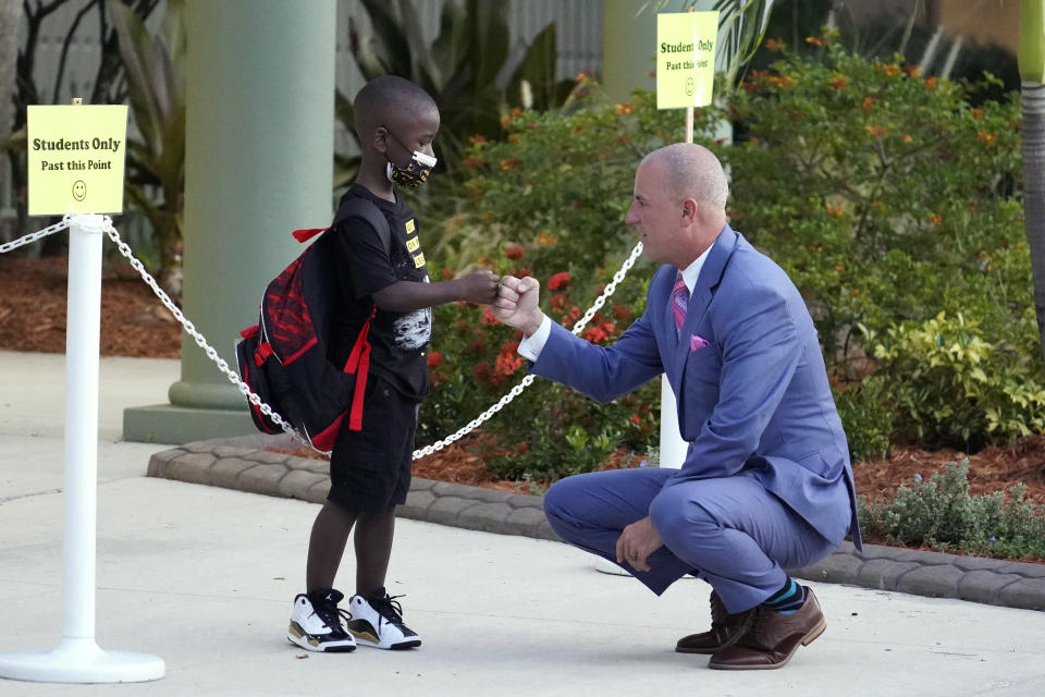 Addison Davis, Hillsborough County Superintendent of Schools, right, fist bumps student James Braden before he heads to class on the first day of school at Sessums Elementary School Tuesday, Aug. 10, 2021, in Riverview, Fla. Students are required to wear protective masks while in class unless their parents opt out. (AP Photo/Chris O'Meara)