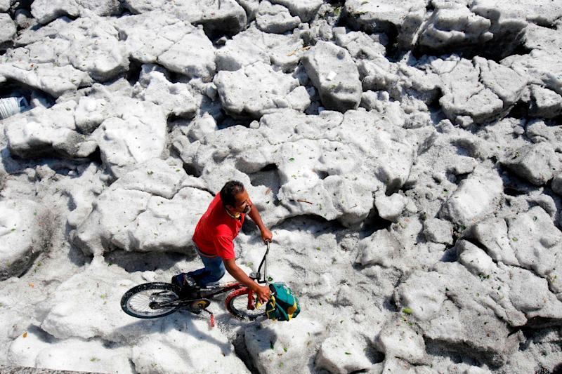 A man with a bike walks on hail in the eastern area of Guadalajara, Jalisco state, Mexico, on June 30, 2019.