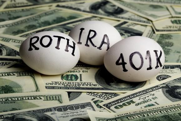 three eggs on which are written the words roth, ira, and 401k, sitting on a bed of hundred dollar bills