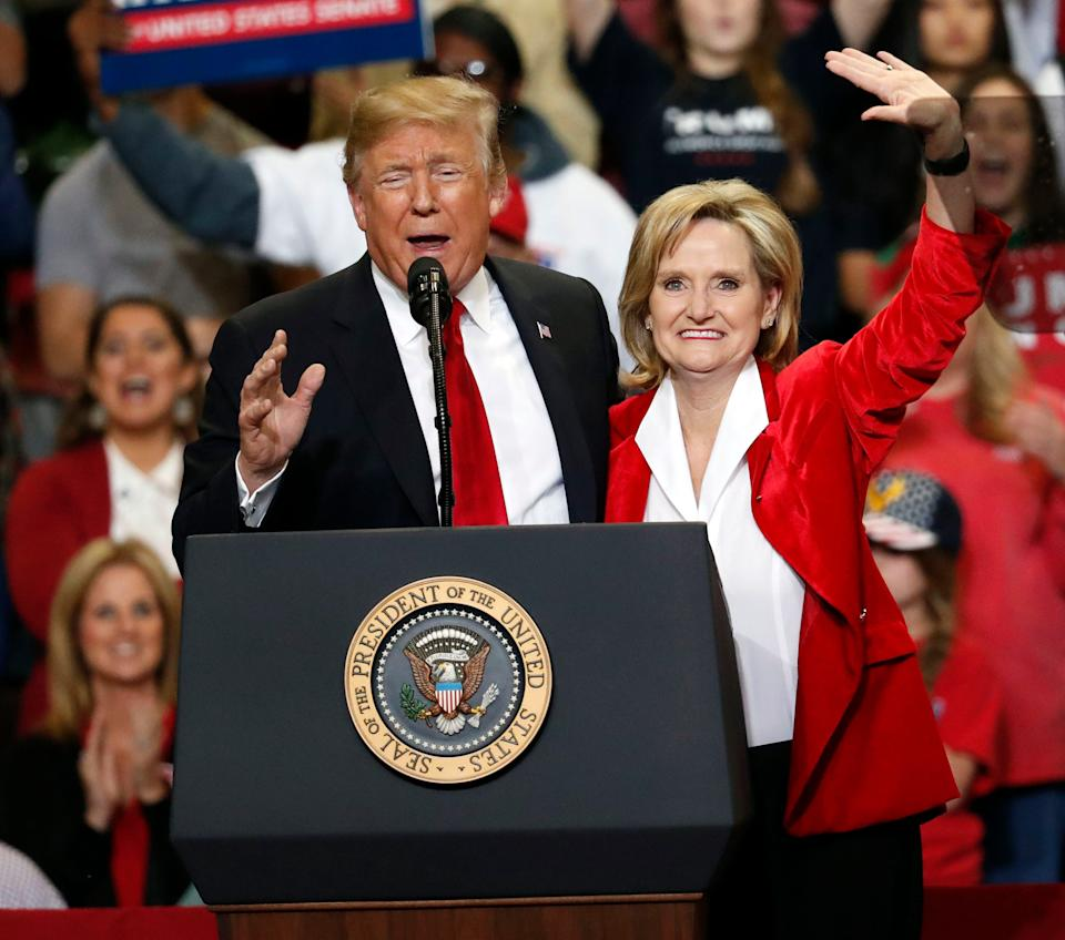In this Nov. 26, 2018 photo, Republican interim senator Cindy Hyde-Smith and President Donald Trump wave during a rally in Biloxi, Miss.