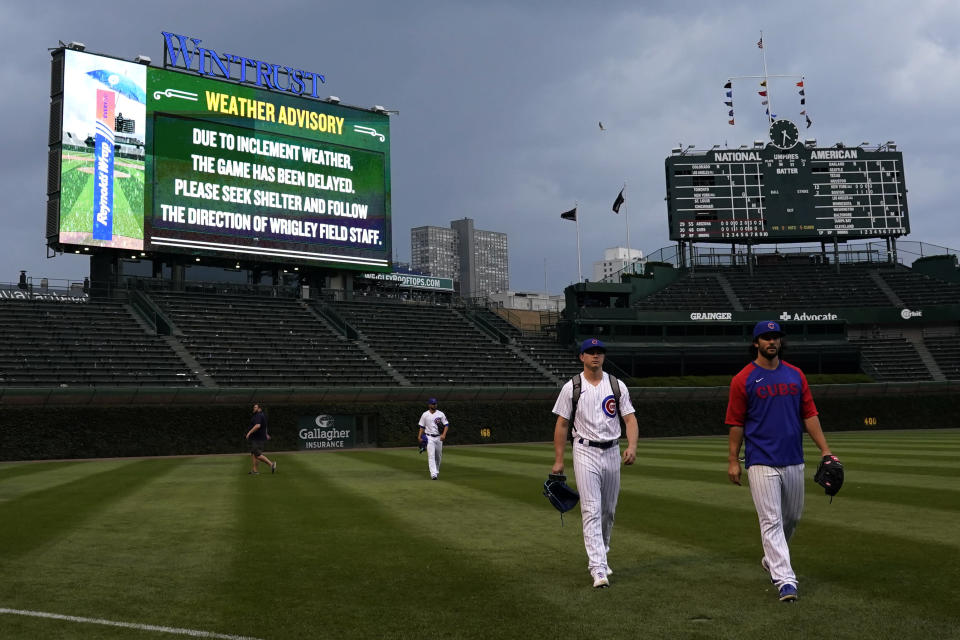 Chicago Cubs players walk to the dugout during a rain delay in the ninth inning of a baseball game against the Arizona Diamondbacks in Chicago, Saturday, July 24, 2021. (AP Photo/Nam Y. Huh)
