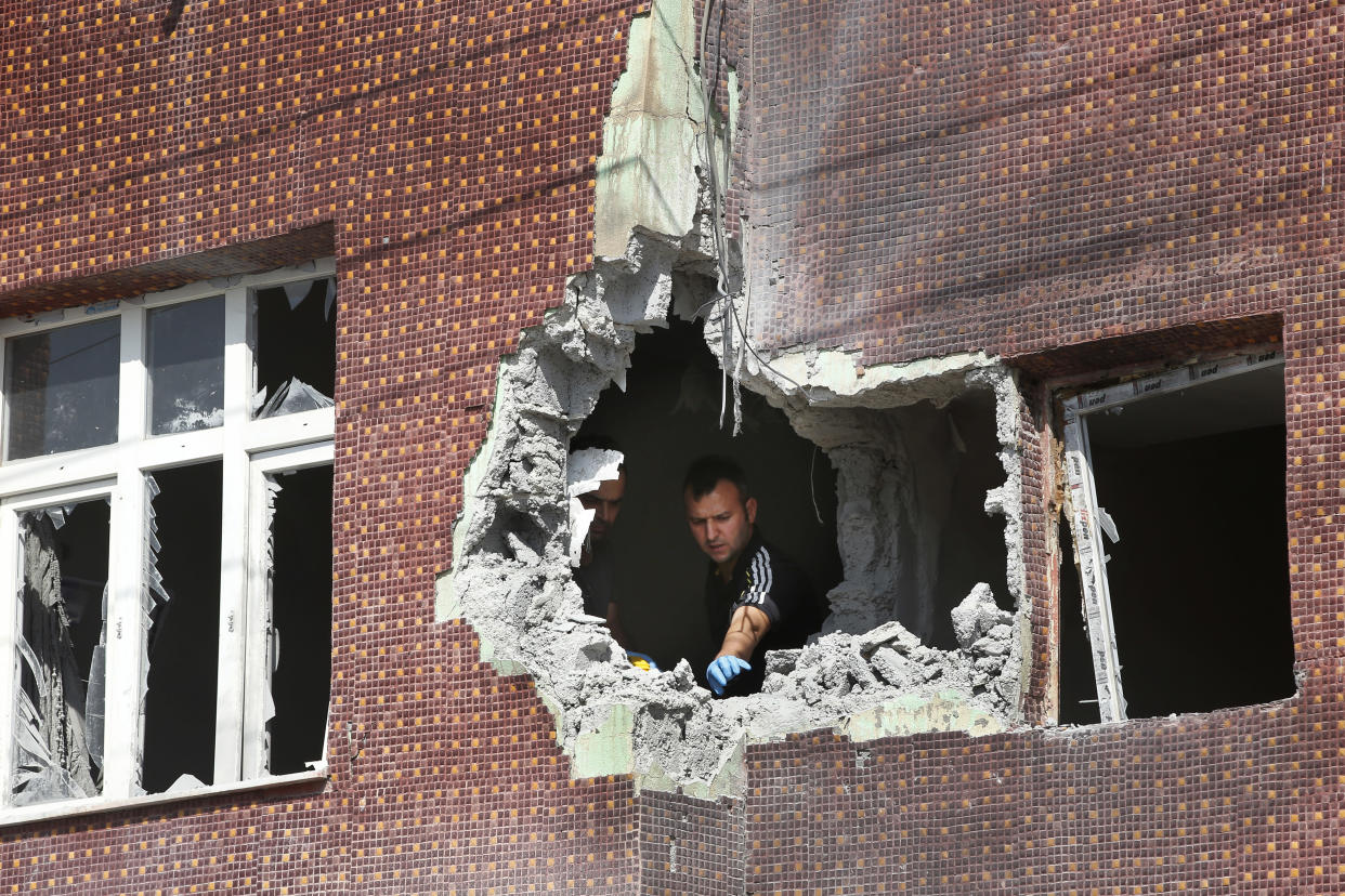 A police forensic officer collects evidence from a building damaged by a mortar fired from inside Syra, in Akcakale, Sanliurfa province, southeastern Turkey, Oct. 13, 2019. (Photo: Lefteris Pitarakis/AP)