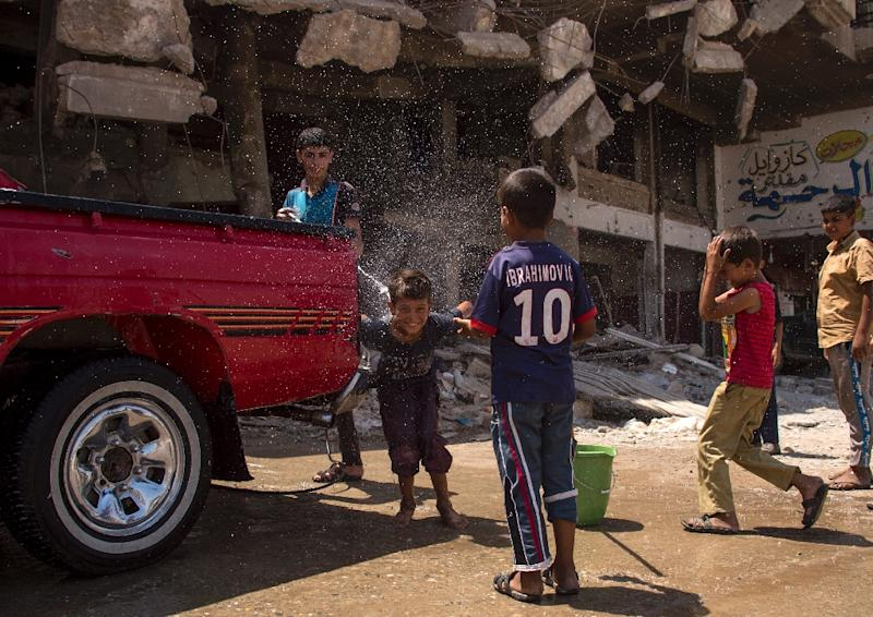 Iraqi boys wash a vehicle in west Mosul on July 12, 2017, days after the government announced the recapture of the city from the Islamic State group