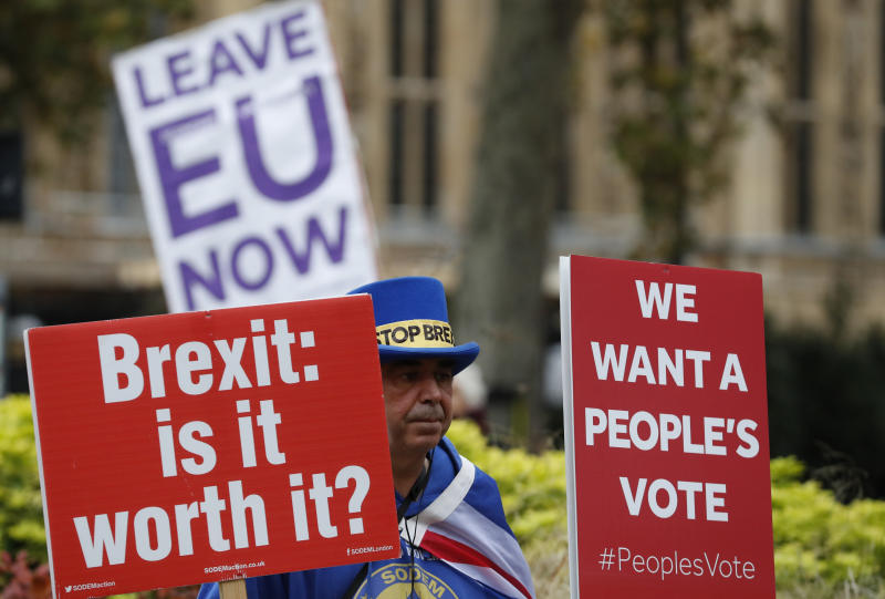 Pro and anti Brexit protesters hold placards as they vie for media attention near Parliament in London, Friday, Nov. 16, 2018. Britain's Prime Minister May still faces the threat of a no-confidence vote, after several Conservative Party lawmakers said they had written letters asking for one. (AP Photo/Alastair Grant)