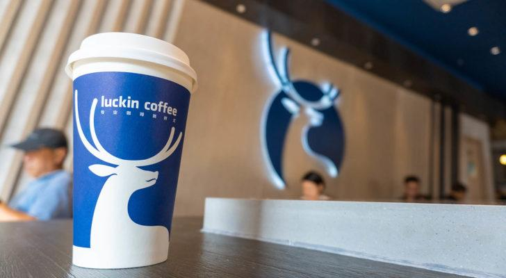 A Luckin (LKNCY) coffee cup on a table in a Luckin shop with the logo on the wall behind.