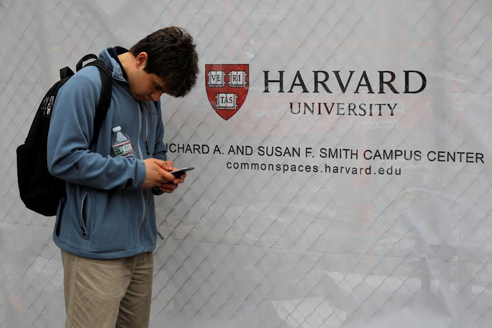 A man looks at his mobile phone beside a sign for Harvard University in Cambridge, Massachusetts, U.S., June 18, 2018. REUTERS/Brian Snyder/File Photo