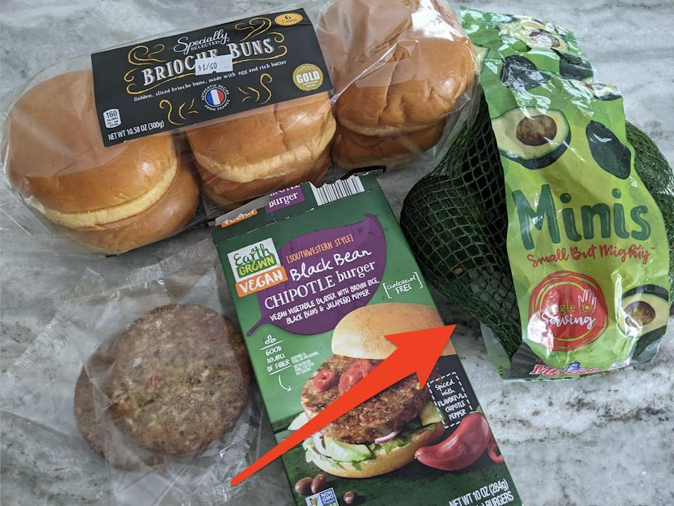 Brioche buns, veggies burgers, and a bag of mini avocados from Aldi on a gray countertop