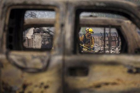 A firefighter is seen through destroyed cars as he searches for victims in the rubble of a home burnt by the Valley Fire in Middletown, California, September 14, 2015. REUTERS/David Ryder