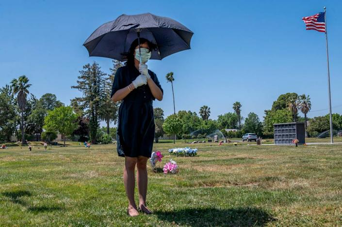 Tracy Nguyen, uses an umbrella to shield the sun while standing alone during the funeral for her boyfriend Dung Tan Nguyen at Sacramento Memorial Lawn on Wednesday, May 6, 2020, during the coronavirus outbreak.