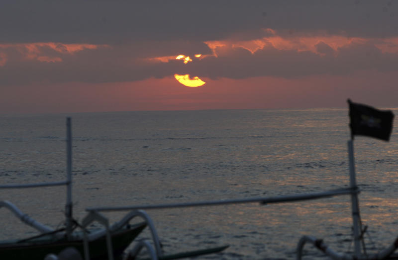 A partial solar eclipse is seen through clouds over Sanur beach, Bali, Indonesia, Friday, May 10, 2013. (AP Photo/Firdia Lisnawati)