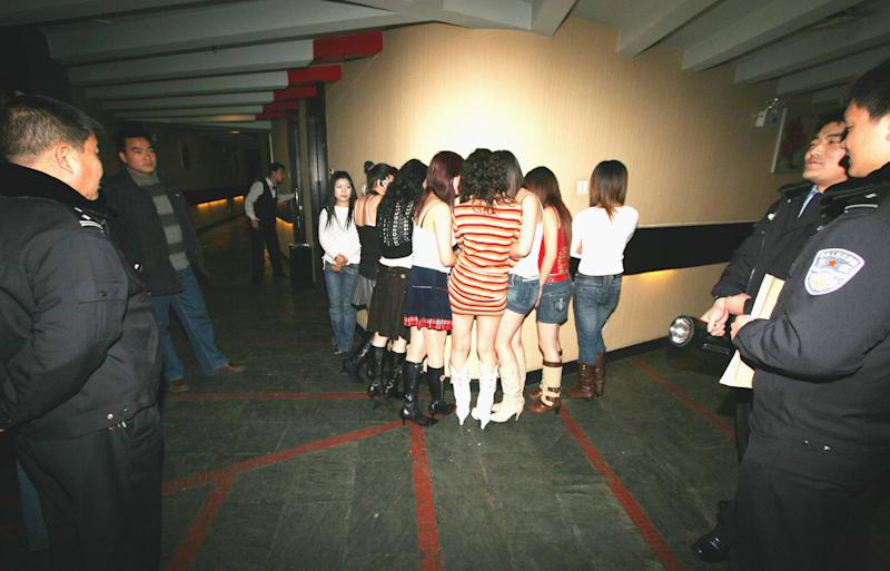 FILE - In this Dec. 11, 2006 file photo, suspected sex workers hide their faces during a police raid at a karaoke lounge in Xuchang, in China's central Henan Province. Police in China frequently beat, torture and arbitrarily detain suspected sex workers, often with little or no evidence that they engaged in prostitution, Human Rights Watch said in a report Tuesday, May 14, 2013, calling on the government to discipline abusive officers. (AP Photo/EyePress, File) CHINA OUT