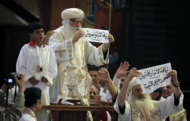 Acting Coptic Pope Pachomios, center, displays the name of 60-year-old Bishop Tawadros, soon to be Pope Tawadros II, while another clergyman displays the names of the remaining two candidates, Bishop Raphael and Father Raphael Ava Mina, during the papal election ceremony at the Coptic Cathedral in Cairo, Egypt, Sunday, Nov. 4, 2012. Egypt's ancient Coptic Christian church chose a new pope in an elaborate Sunday ceremony meant to invoke the will of God, in which a blindfolded boy drew the name of the next patriarch from a crystal chalice. (AP Photo/Nasser Nasser)