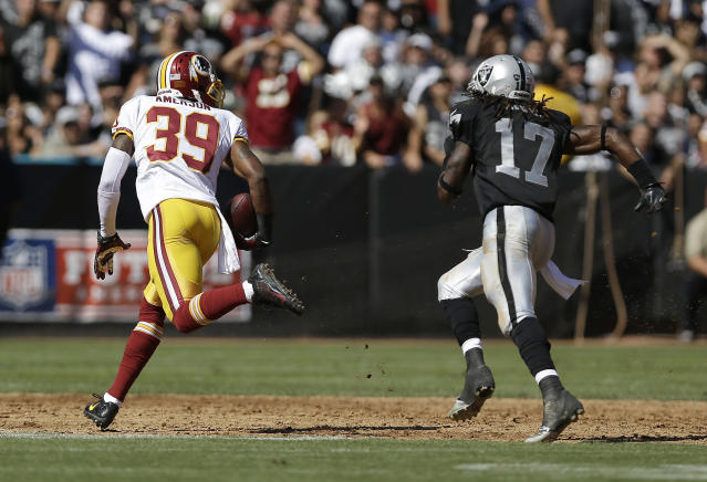 Washington Redskins free safety David Amerson (39) runs from Oakland Raiders wide receiver Denarius Moore (17) to return an interception for a 45-yard touchdown during the second quarter of an NFL football game in Oakland, Calif., Sunday, Sept. 29, 2013. (AP Photo/Marcio Jose Sanchez)