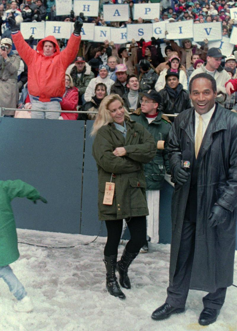 FILE - In this Nov 25 1993 file photo, O.J. Simpson stands with his wife Nicole Brown Simpson on the sidelines during the Thanksgiving Day game between the Dallas Cowboys and the Miami Dolphins at Texas Stadium in Irving, Texas. The return of O.J. Simpson to a Las Vegas courtroom next Monday, May, 13, 2013 will remind Americans of a tragedy that became a national obsession and in the process changed the country's attitude toward the justice system, the media and celebrity. (AP Photo/Ron Heflin, File)