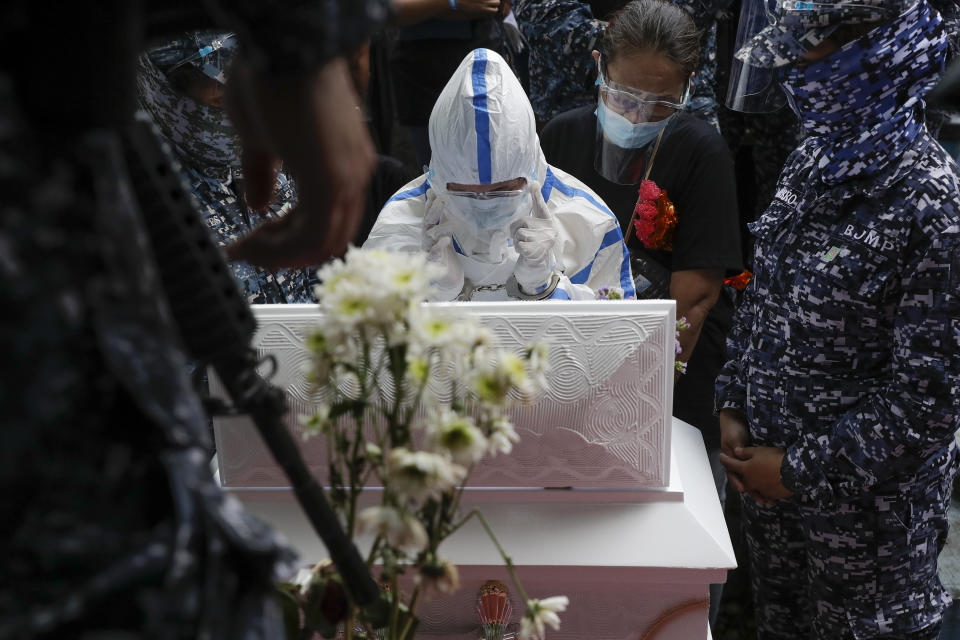 Detained left-wing activist Reina Mae Nasino in handcuffs and wearing protective suit to prevent the spread of the coronavirus grieves in front of the coffin of her three-month-old firstborn named River during funeral rites at Manila's North Cemetery, Philippines on Friday Oct. 16, 2020. Left-wing groups on Friday decried the treatment as brutal of Nasino, who was allowed by a Manila court to attend her baby's burial but was restrained with handcuffs, a sweltering protective suit and swarms of armed escorts as she quietly wept. (AP Photo/Aaron Favila)