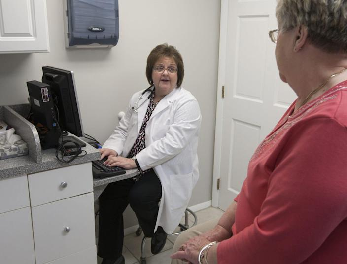 Dr. Diane G. Verga, a physician with Hooper Ave. Adult Care in Toms River, N.J., talks with patient Carol Nering on March 25, 2013, as she checks Nering's electronic medical record on a computer. Telemedicine in New Jersey is more evolution than revolution. That's because the first step toward telemedicine is linking systems and sharing data, which begins with computerization of medical records. Proposed telemedicine laws have yet to find their way out of legislative committees. (Gannett, Bob Bielk/Asbury Park Press) [Via MerlinFTP Drop]