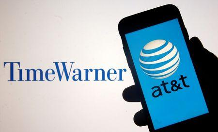 Smartphone with AT&T logo is seen in front of displayed Time Warner logo in this picture illustration