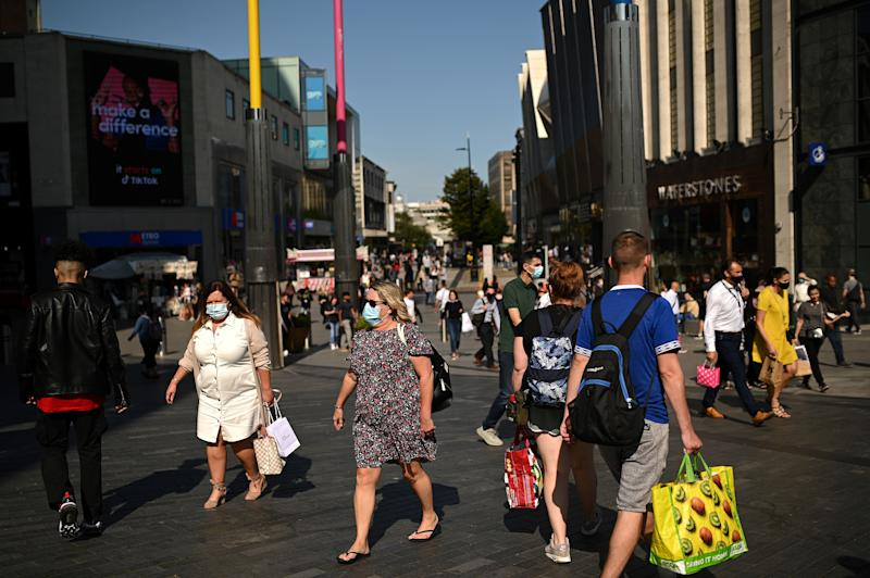 Pedestrians, some wearing a face mask or covering due to the COVID-19 pandemic, walk along a busy shopping street in Birmingham, central England on September 14, 2020 after the British government imposed fresh restrictions on the city after an rise in cases of the novel coronavirus. - Authorities in Britain's second city of Birmingham announced new coronavirus restrictions Friday as the nation's viral reproduction rate, or R number, exceeded 1.0 for the first time since March. (Photo by Oli SCARFF / AFP) (Photo by OLI SCARFF/AFP via Getty Images)