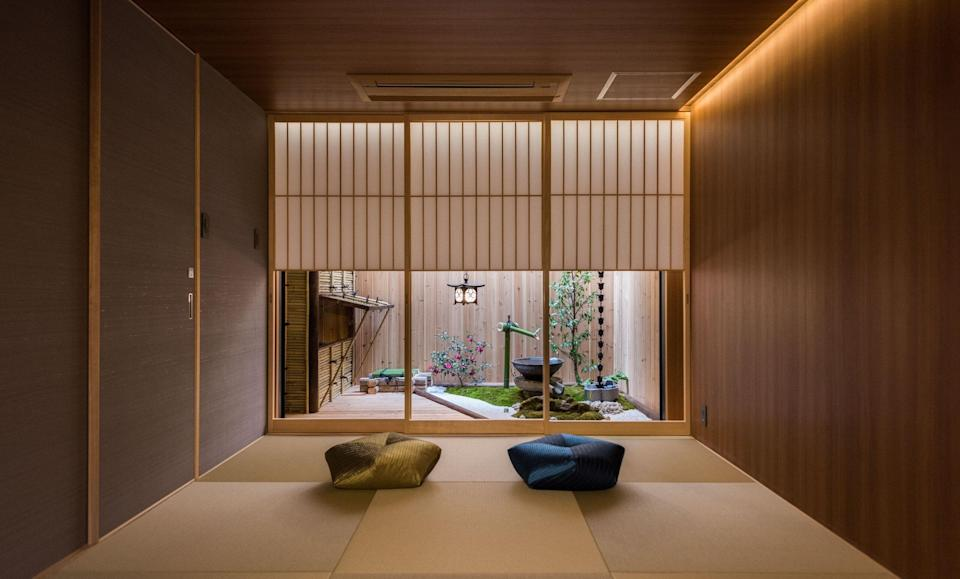 """<p>A short walk from Nijō station, this Airbnb is in the center of busy <a href=""""https://www.cntraveler.com/story/kyoto-beyond-the-temples-and-shrines?mbid=synd_yahoo_rss"""" rel=""""nofollow noopener"""" target=""""_blank"""" data-ylk=""""slk:Kyoto"""" class=""""link rapid-noclick-resp"""">Kyoto</a>—but you wouldn't know from its serene interior. The calming Japanese garden is the centerpiece of the home, complete with a water feature and small trees, and adjoining traditional circular bathtub. A small kitchenette is also found on the first floor. Upstairs, a tatami-style bedroom and ensuite bathroom. (You can also convert the pictured living room into a bedroom if you have more than two guests.)</p> <p><strong>Book now:</strong> <a href=""""https://airbnb.pvxt.net/jq1Ae"""" rel=""""nofollow noopener"""" target=""""_blank"""" data-ylk=""""slk:From $115 per night, airbnb.com"""" class=""""link rapid-noclick-resp"""">From $115 per night, airbnb.com</a></p>"""