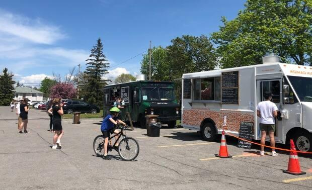People stay physically distanced as they wait in line to order at food trucks set up in Parc des Cedres in Gatineau, Que., on May 15, 2021. (Marielle Guimond/Radio-Canada - image credit)