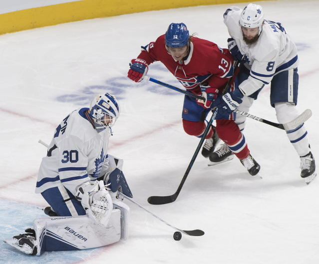 Montreal Canadiens' Max Domi (13) moves in on Toronto Maple Leafs goaltender Michael Hutchinson as Leafs' Jake Muzzin defends during the first period of an NHL hockey game, in Montreal, Saturday, Oct. 26, 2019. (Graham Hughes/The Canadian Press via AP)
