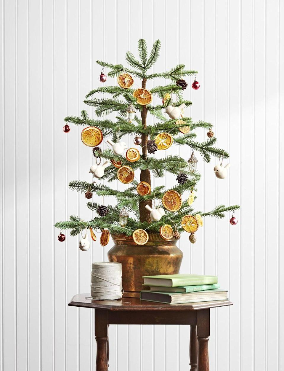 "<p>Citrus ornaments look almost like stained glass when the light shines through them. To string your own strand, all you need are navel and blood oranges, parchment paper, two cookie sheets, jute or natural twine, a skewer or nail, and decorative hooks. </p><p><strong>Make the Ornaments:</strong></p><p>1. Preheat oven to 250°F. </p><p>2. Cut oranges crosswise into 1/4-inch slices (four oranges make a six-foot garland). </p><p>3. Line cookie sheets with parchment paper. Pat orange slices dry with paper towels, and place them on cookie sheets in a single layer. </p><p>4. Bake for approximately 3 hours or until dry. (To ensure the slices dry flat, turn them over at the midway mark.) Remove from oven. </p><p>5. Using a skewer or nail, poke two holes into the top of each orange slice. </p><p>6. Thread twine through each hole, evenly spacing the oranges on the garland. Tie off each end with a loop, and hang from hooks.</p><p><a class=""link rapid-noclick-resp"" href=""https://www.amazon.com/Jansal-Valley-Natural-Sliced-Oranges/dp/B00MBFRVFO/ref=sr_1_9?tag=syn-yahoo-20&ascsubtag=%5Bartid%7C10050.g.1070%5Bsrc%7Cyahoo-us"" rel=""nofollow noopener"" target=""_blank"" data-ylk=""slk:SHOP DRIED ORANGE SLICES"">SHOP DRIED ORANGE SLICES</a></p>"