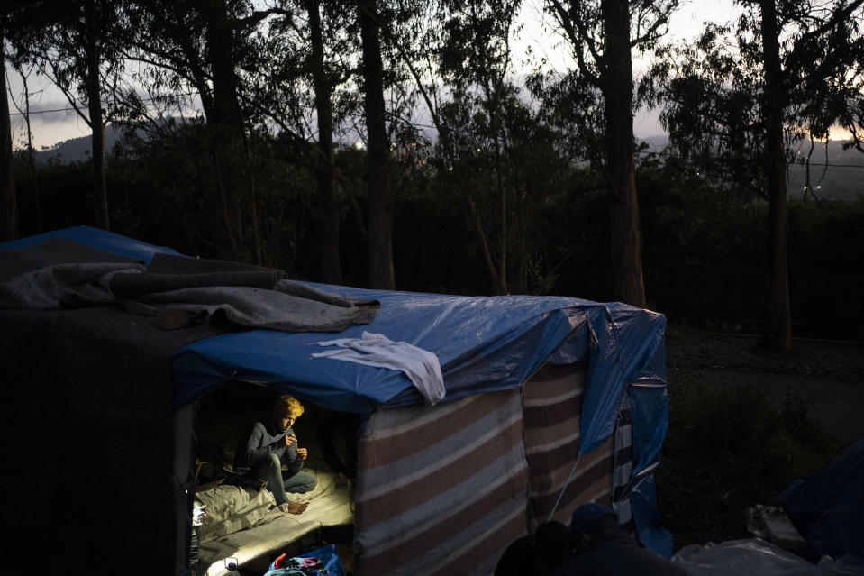 A migrant rests in a makeshift shelter in Las Raices camp in San Cristobal de la Laguna on the Canary Island of Tenerife, Spain, Wednesday, March 17, 2021. Several thousand migrants have arrived on the Spanish archipelago in the first months of 2021. Due to the terrible living conditions and the poor quality of food and water, some migrants have decided to leave the camp and sleep in shacks in a nearby forest instead. (AP Photo/Joan Mateu)