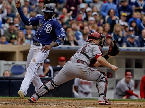 San Diego Padres' Cameron Maybin, left, races past Arizona Diamondbacks catcher Miguel Montero while beating the throw and scoring on a base hit by Yonder Alonso during the fourth inning of a baseball game on Saturday, June 2, 2012, in San Diego. (AP Photo/Lenny Ignelzi)