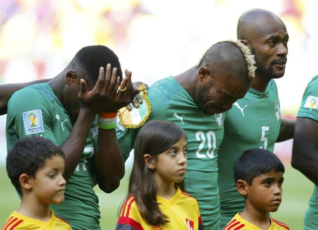 Ivory Coast's Serge Aurier, Geoffroy Serey Die and Didier Zokora react as they sing their national anthem before the 2014 World Cup Group C soccer match betweem Colombia and Ivory Coast at the Brasilia national stadium in Brasilia June 19, 2014. REUTERS/Paul Hanna (BRAZIL - Tags: SOCCER SPORT WORLD CUP)