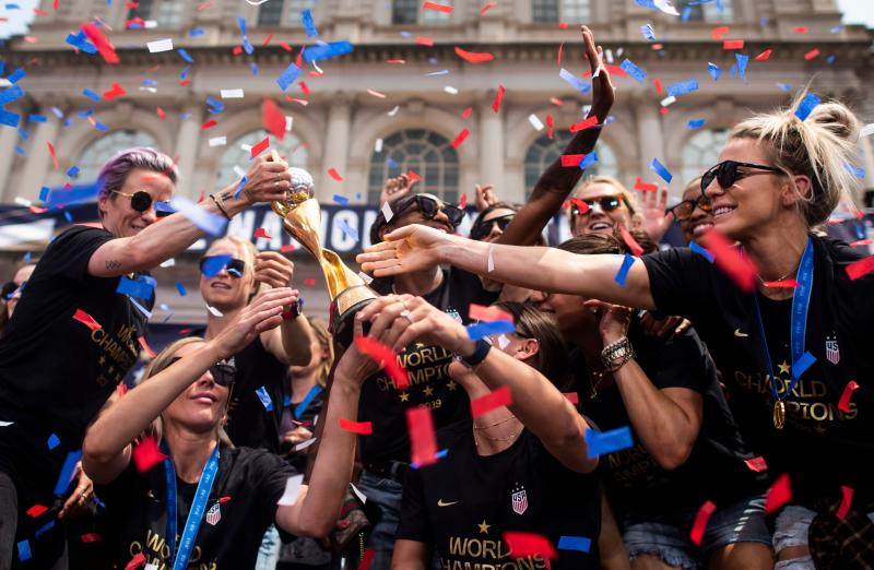 """Members of the World Cup-winning US women's team take part in a ticker tape parade with their trophy for the women's World Cup champions on July 10, 2019 in New York. - Tens of thousands of fans are poised to pack the streets of New York on Wednesday to salute the World Cup-winning US women's team in a ticker-tape parade. Four years after roaring fans lined the route of Lower Manhattan's fabled """"Canyon of Heroes"""" to cheer the US women winning the 2015 World Cup, the Big Apple is poised for another raucous celebration. (Photo by Johannes EISELE / AFP) (Photo credit should read JOHANNES EISELE/AFP/Getty Images)"""
