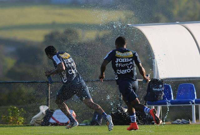 Honduran team players throw water at each other at the end of a training session of the Honduran national soccer team, in Porto Feliz, Brazil, Sunday, June 22, 2014. Languishing in bottom spot in Group E after two defeats, Honduras has only a very slim chance of qualifying for the knockout stages of the World Cup. (AP Photo/Fernando Antonio)