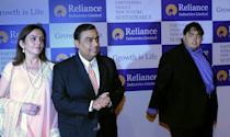 Chairman of Reliance Industries Limited Mukesh Ambani (C) arrives for the company's annual general meeting with his wife Nita (L) and son Anant (R) in Mumbai, on June 7, 2012. Controlled by the elder of the two Ambani brothers, shares of Reliance Industries are held by one out of every four Indian investors. AFP PHOTO/ Indranil MUKHERJEE