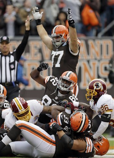 Cleveland Browns guard John Greco (77) and tight end Benjamin Watson (82) celebrate as running back Trent Richardson (33) scores on a 6-yard run against the Washington Redskins in the first quarter of an NFL football game on Sunday, Dec. 16, 2012, in Cleveland. (AP Photo/Tony Dejak)